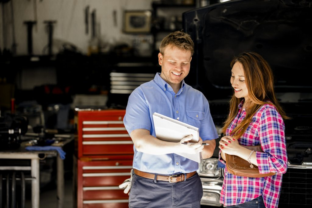 Happy customer discusses repairs with auto mechanic at Mike Calvert Toyota Collision Center